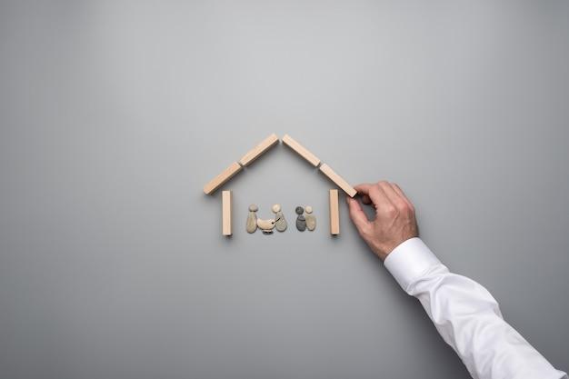 Mão masculina que faz uma casa de pinos de madeira em torno de uma família feita de seixos em uma imagem conceitual.