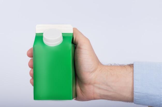 Mão masculina que guarda o pacote verde para o leite ou o suco no fundo branco. copie o espaço, mock up