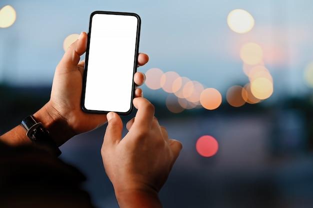 Mão masculina que guarda o telefone esperto móvel da tela vazia na noite da rua.