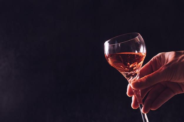 Mão masculina que guarda um vidro do vinho no fundo preto. espaço livre para o texto