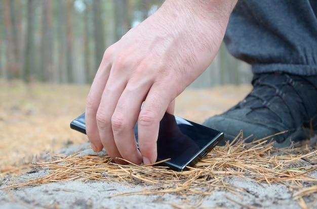 Mão masculina que pega o telefone móvel perdido de uma terra no trajeto da madeira do abeto do outono. o conceito de encontrar algo valioso e boa sorte