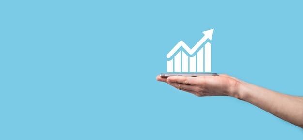 Mão masculina que prende o telefone móvel inteligente com o gráfico icon.checking, analisando o gráfico de gráfico de crescimento de dados de vendas e o mercado de ações na rede global.