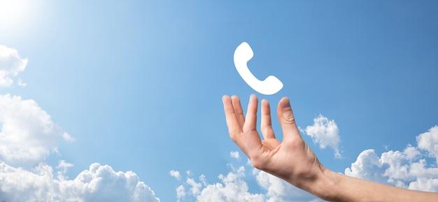 Mão masculina que prende o telefone móvel inteligente com o ícone do telefone. ligue agora conceito de tecnologia de serviço ao cliente do centro de suporte de comunicação empresarial.