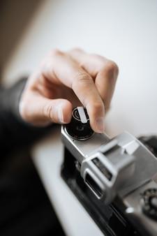 Mão masculina que recarrega a câmera retro do filme em uma tabela branca. horizontal