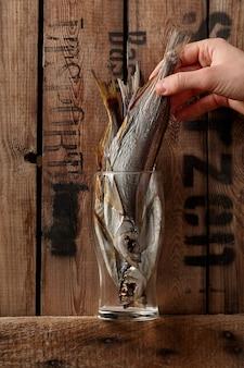 Mão masculina retirando sabrefish salgados e secos de vidro