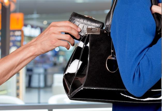 Mão masculina roubando carteira de bolsa feminina