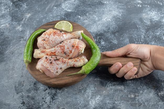 Mão masculina segura a tábua de cortar. pernas de frango cru.