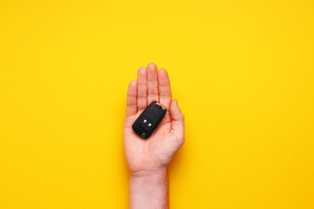 Mão masculina segura as chaves do carro em fundo amarelo. carro-conceito, aluguel de carro, presente, aulas de direção, carta de condução. camada plana, vista superior