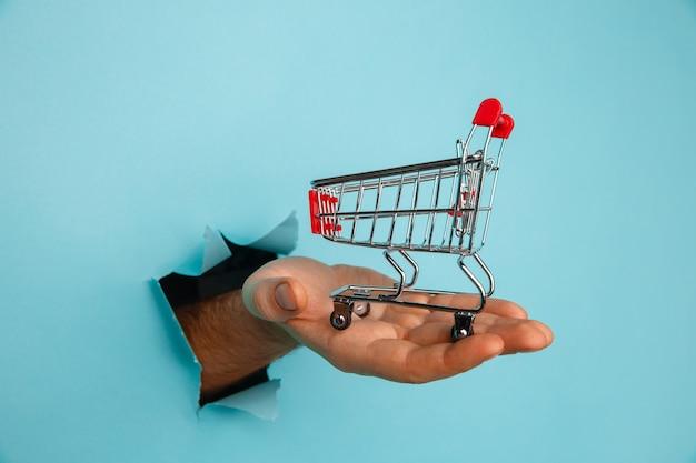 Mão masculina segura através de um buraco um mini carrinho de compras de supermercado em um fundo de papel azul. conceito de vendas.