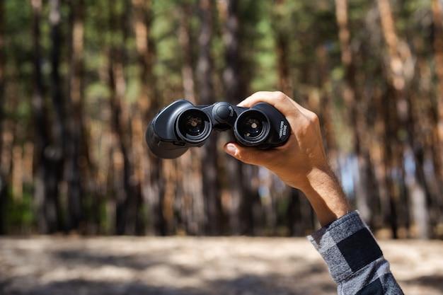 Mão masculina segura binóculos na floresta