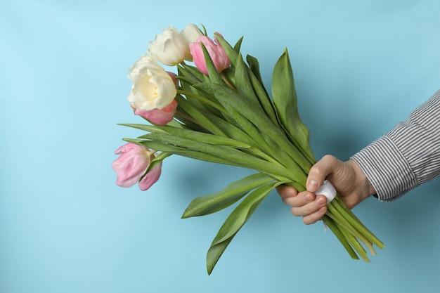 Mão masculina segura buquê de tulipas em fundo azul