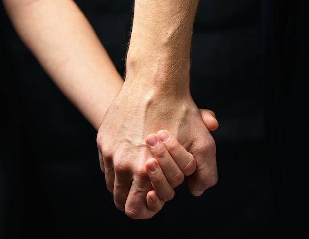 Mão masculina segura mão feminina em fundo escuro