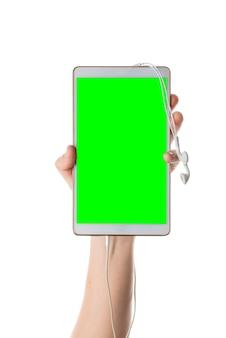 Mão masculina segura tablet branco com fones de ouvido conectados tela isolada com chroma key