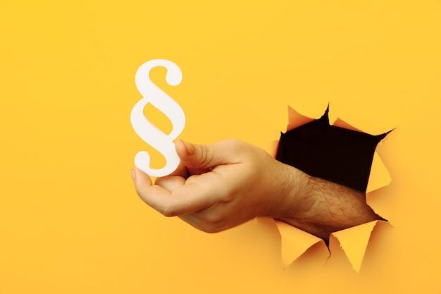 Mão masculina segura um parágrafo como um sinal de justiça e lei através de um buraco de papel amarelo.