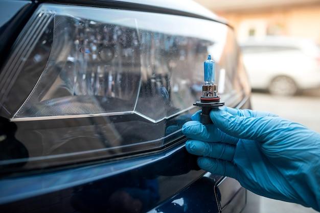 Mão masculina segura uma lâmpada halógena contra os faróis, tudo para consertar o carro