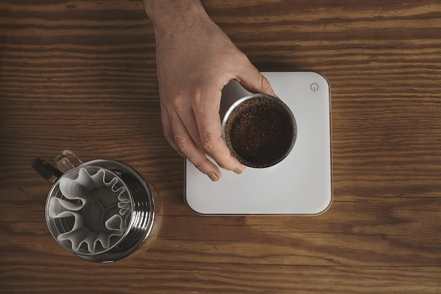 Mão masculina segura uma xícara de prata inoxidável com café moído torrado acima de pesos simples brancos. goteje cafeteira para café filtrado próximo. tudo na mesa de madeira grossa na loja do café. vista do topo.