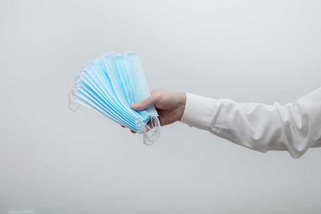 Mão masculina segura várias máscaras médicas no fundo claro