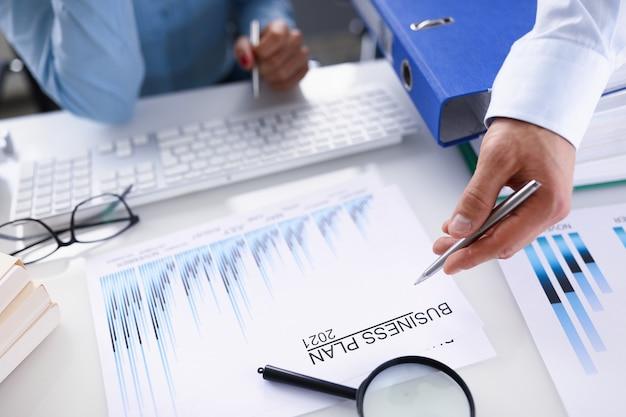 Mão masculina segurando a caneta esferográfica sobre o plano de negócios para 2021 closeup e mão feminina com teclado