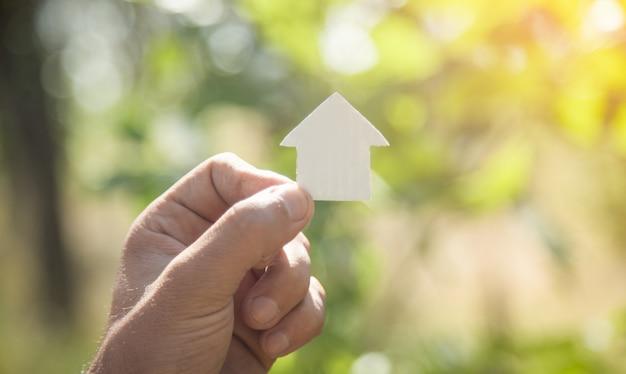 Mão masculina segurando a casa de papel na natureza.