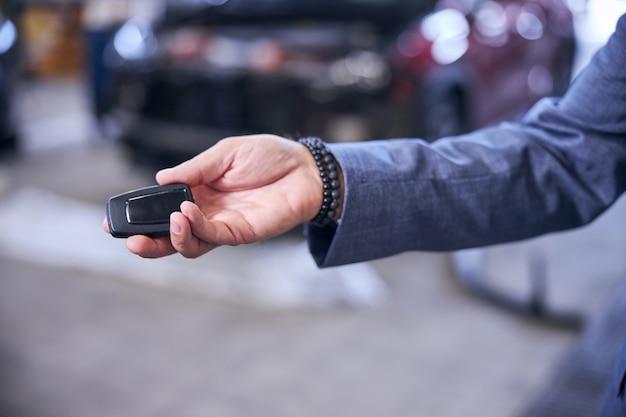 Mão masculina segurando a chave do carro eletrônico moderno