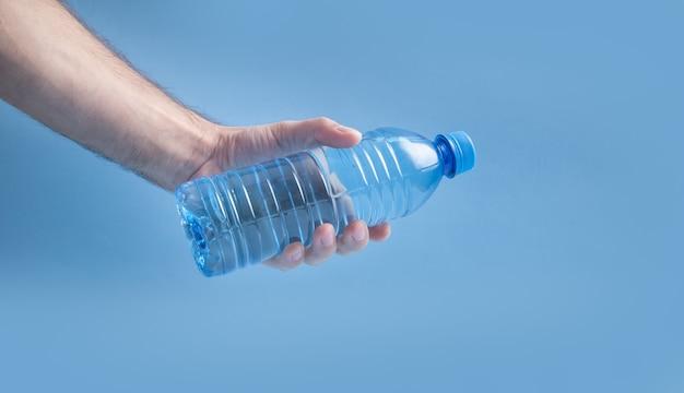 Mão masculina segurando a garrafa de água de plástico.