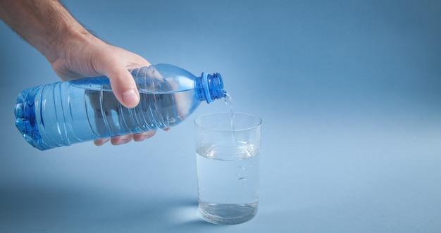 Mão masculina segurando a garrafa de água derramando água no copo.
