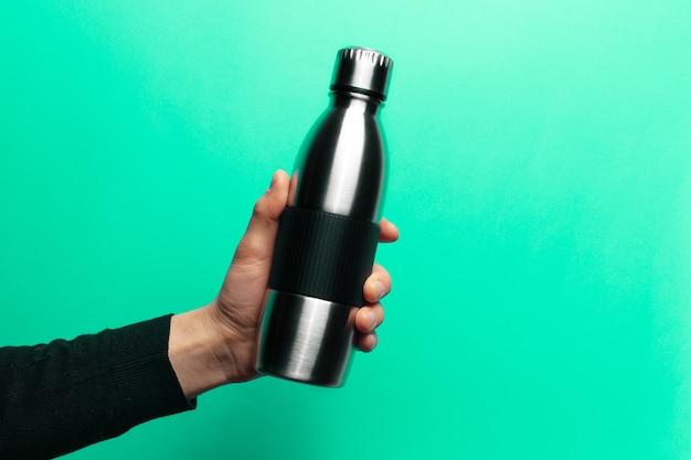 Mão masculina segurando a garrafa térmica reutilizável de aço para água sobre fundo verde.