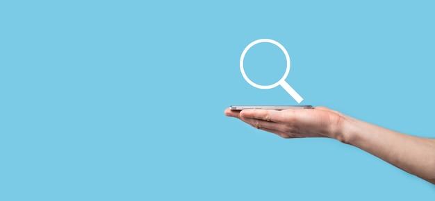 Mão masculina segurando a lupa, ícone de pesquisa sobre fundo azul. otimização de mecanismo de busca de conceito, suporte ao cliente. informação de dados de internet de navegação. conceito de rede.