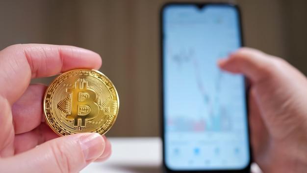Mão masculina segurando a moeda criptomoeda e celular mostrando o gráfico.