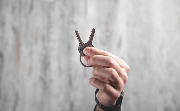 Mão masculina segurando as chaves da casa. imobiliária