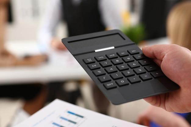 Mão masculina segurando calculadora no escritório