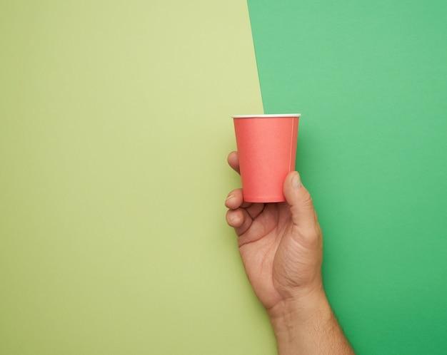 Mão masculina segurando copo descartável de papel vermelho, conceito ecológico, desperdício zero