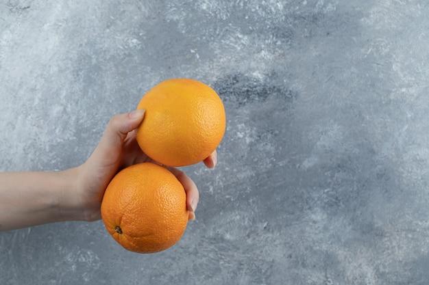Mão masculina segurando duas laranjas na mesa de mármore.