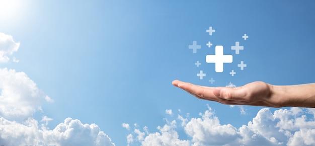 Mão masculina segurando mais o ícone sobre fundo azul. sinal de mais significa virtual para oferecer coisas positivas como benefícios, desenvolvimento pessoal, rede social lucro, seguro saúde, conceitos de crescimento