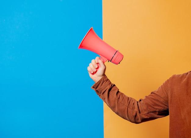 Mão masculina segurando megafone rosa em fundos azuis e amarelos