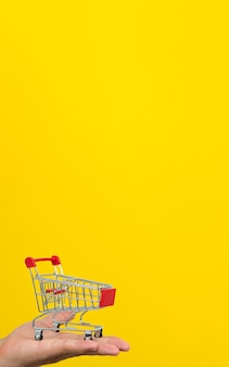Mão masculina segurando o carrinho de compras pequeno carrinho em fundo amarelo.