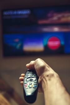 Mão masculina segurando o controle remoto da tv.