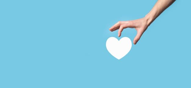 Mão masculina segurando o coração, como ícone sobre fundo azul. conceito de bondade, caridade, amor puro e compaixão. bandeja com espaço de cópia.