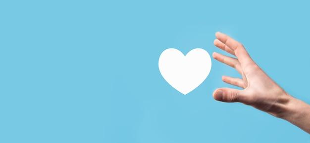 Mão masculina segurando o coração, como ícone sobre fundo azul. conceito de bondade, caridade, amor puro e compaixão.