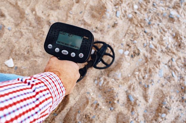 Mão masculina segurando o dispositivo detector de metais acima do solo