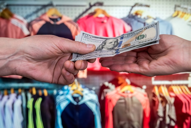 Mão masculina segurando o dólar na loja de roupas para compra. dinheiro