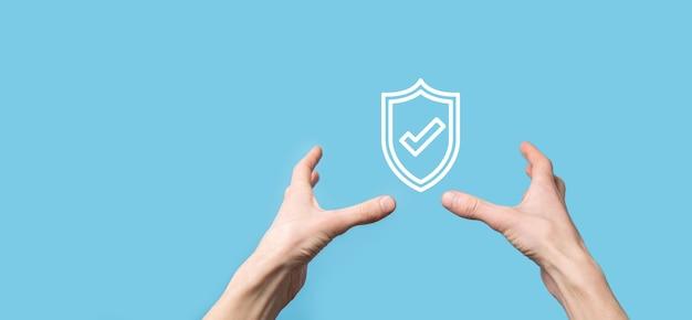Mão masculina segurando o escudo protetor com um ícone de marca de seleção na superfície azul