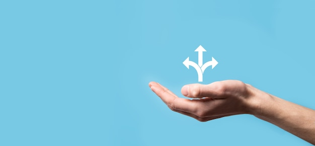 Mão masculina segurando o ícone com o ícone de três direções em fundo azul. dúvida tendo que escolher entre três opções diferentes indicadas por setas apontando na direção oposta