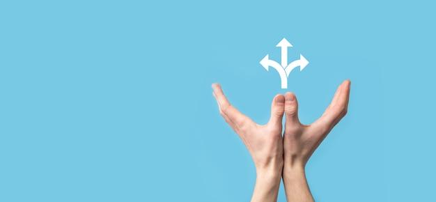 Mão masculina segurando o ícone com o ícone de três direções no fundo azul. dúvida tendo que escolher entre três opções diferentes indicadas por setas apontando na direção oposta conceito três maneiras