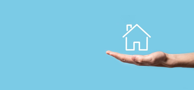 Mão masculina segurando o ícone da casa sobre fundo azul. conceito de seguro e segurança de propriedade. conceito de bens imobiliários. bandeira com espaço de cópia.