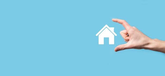 Mão masculina segurando o ícone da casa sobre fundo azul. seguro de propriedade e conceito de segurança. conceito de bens imobiliários.