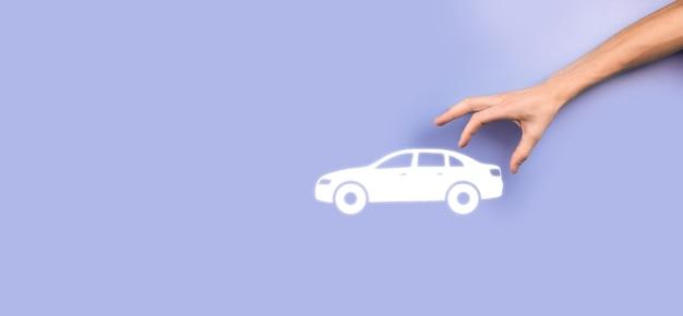 Mão masculina segurando o ícone de carro auto em fundo cinza. composição de faixa ampla. conceitos de renúncia de danos de colisão e seguro automóvel automóvel.