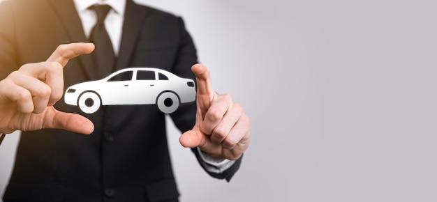Mão masculina segurando o ícone de carro auto em fundo cinza. composição de faixa ampla. conceitos de seguro de automóvel e isenção de danos por colisão