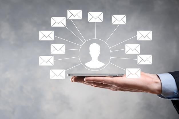 Mão masculina segurando o ícone de carta, ícones de e-mail. entre em contato conosco por e-mail de boletim informativo e proteja suas informações pessoais de mensagens de spam. call center de atendimento ao cliente entre em contato conosco. e-mail marketing e newsletter.