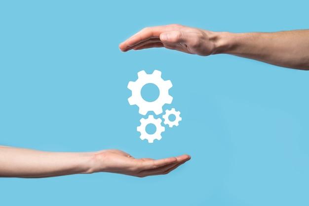 Mão masculina segurando o ícone de engrenagens, ícone do mecanismo em telas virtuais sobre fundo azul. conceito de negócio do sistema de processo de tecnologia de software de automação. bandeira.
